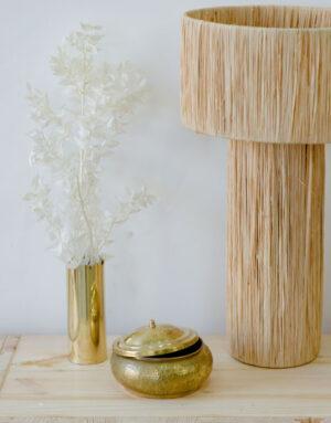 Boite dorée entourée d'un vase et d'une lampe